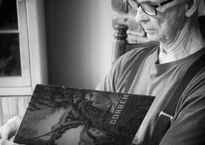 Richard Corben seated and looking through 2018 Corben Angouleme catalog.