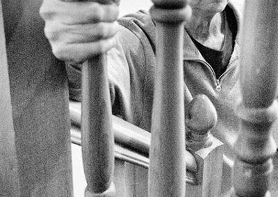 Richard Corben peering through railings while gripping one rail foreshortened view.
