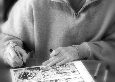 Richard Corben signing original comic art while seated at table
