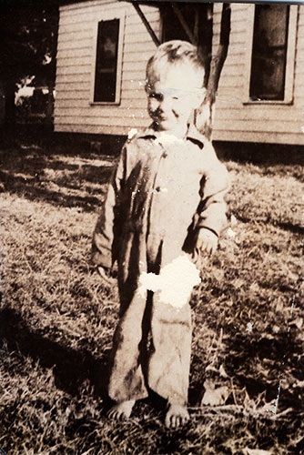 Richard Corben at 4 years old in front of the house he was born in.