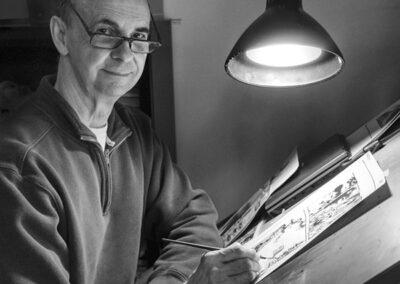 Richard Corben drawing a comic page at his desk.